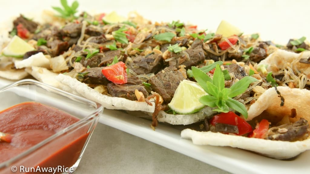 Beef Stir-Fry Appetizer / Bo Xao Lan - Beef Stir-Fry with Cellophane Noodles, Red Bell Peppers, Wood Ear Mushrooms and Rice Paddy Herb Served over Crispy Sesame Rice Crackers with a Side of Sriracha Hot Sauce | recipe from runawayrice.com